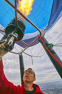 A balloon pilot adjusting the burning gas jets that heat air inside the balloon, during the Bristol International Balloon Fiesta, England, United Kingdom, Europe