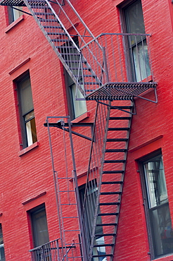 Red painted tenement block and fire escapes, New York, United States of America, North America