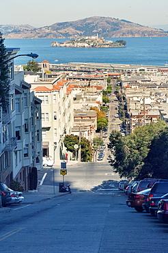 Steep city street, San Francisco with the prison island of Alcatraz in the bay, San Francisco, California, United States of America, North America
