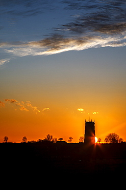 Sunset behind the Parish Church of the Holy Trinity and All Saints at Winterton on Sea, Norfolk, England, United Kingdom, Europe
