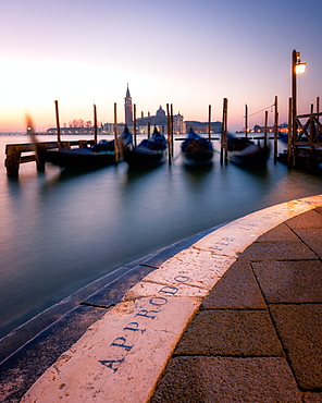 Long exposure of gondolas by San Giorgio Maggiore at sunset in Venice, Italy, Europe