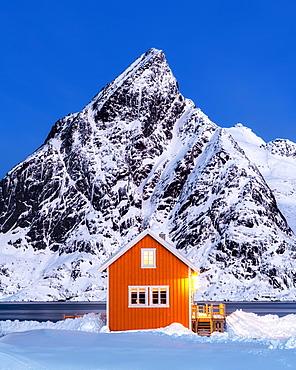 Yellow rorbuer hut in the snow at twilight, Sakrisoy, Moskenesoya, Lofoten Islands, Nordland, Norway, Europe