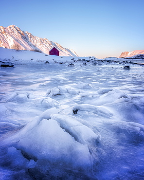 Red rorbuer hut set against a frozen lake, Lofoten Islands, Nordland, Norway, Europe