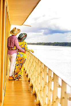 Couple enjoying the view of the Amazon River aboard a river boat, Peru, South America
