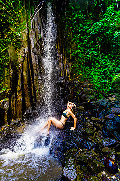 Woman posing for a picture under a waterfall at the Beji Guwang Hidden Canyon, Bali, Indonesia, Southeast Asia, Asia