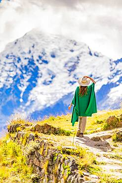 Woman enjoying the view high in the Andes Mountains while exploring Inti Punku (Sun Gate), Cusco, Peru, South America