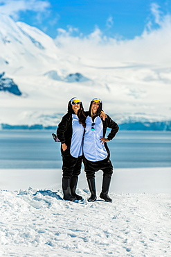 Two American women tourists in Penguin Onesies on sunny day, posing on the glaciers, Antarctica, Polar Regions
