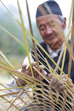A old Nepali man makes a traditional basket by weaving bamboo, Kathmandu Valley, Nepal, Asia