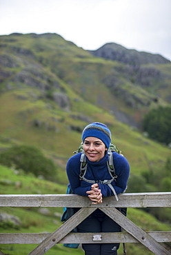 A woman rests on a gate in the Great Langdale valley in The Lake District, Cumbria, England, United Kingdom, Europe