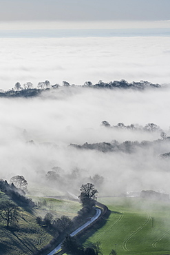 Mist and winter sunlight over Kilburn village and the Vale of York from above the White Horse of Kilburn, Yorkshire, England, United Kingdom, Europe