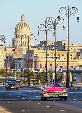 Vintage cars at El Malecon, Centro Habana and El Capitolio at sunset, Havana, La Habana Province, Cuba, West Indies, Central America