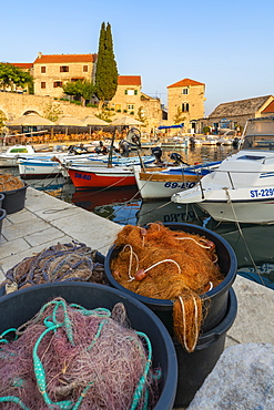 Boats and fishing nets at the pier of the town at sunset, Bol, Brac island, Split-Dalmatia county, Croatia, Europe