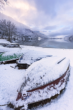 Boats covered by snow at Poschiavo Lake (Lago di Poschiavo), Poschiavo Valley (Val Poschiavo), Graubunden, Switzerland, Europe