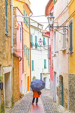 A person with an umbrella in the main street of Civezza, Province of Imperia, Liguria, Italy, Europe
