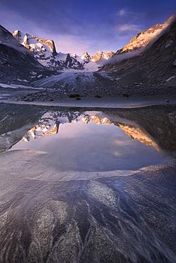 Sunrise reflected in a pond at Forno Glacier, Forno Valley, Maloja Pass, Engadine, Graubunden, Switzerland, Europe