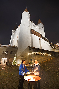 A couple of people warm their hands with the castle in the background, Thun, Canton of Bern, Switzerland, Europe