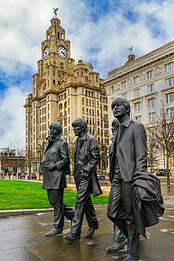 The Beatles statue, bronze art depicting the famous band facing river Mersey with Royal Liver Building in the background, Liverpool, Merseyside, England, United Kingdom, Europe