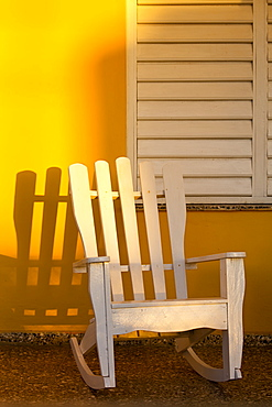 White rocking chair on yellow porch, Vinales, UNESCO World Heritage Site, Cuba, West Indies, Caribbean, Central America