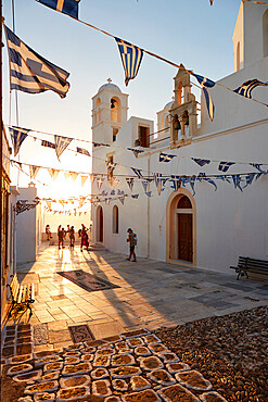 Sunset in Plaka, the main town on Milos, with Greek Orthodox feast decoration on the church square with pebble mosaic, Plaka, Milos, Cyclades, Greek Islands, Greece, Europe