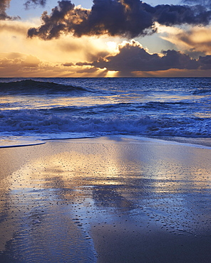 Early morning light glistening on the wet sand with dramatic clouds beyond, Porthcurno, Cornwall, England, United Kingdom, Europe