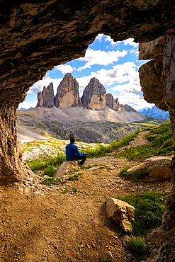 Hiker admires the three peaks of Lavaredo from the caves, Natural Park of the Three Peaks, Trentino-Alto Adige, Italy, Europe