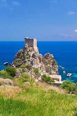 View across field to ruined medieval watchtower on cliffs above the Gulf of Castellammare, Scopello, Trapani, Sicily, Italy