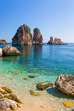 View across tranquil cove to the Faraglioni, a series of towering offshore rock stacks, Scopello, Trapani, Sicily, Italy, Mediterranean, Europe