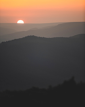 A beautiful sunset with the sun just dipping behind the hills in the Peak District National Park, Derbyshire, England, United Kingdom, Europe