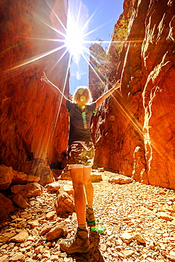 Carefree tourist woman enjoying the picturesque natural alleyway of Standley Chasm as mid-day sun rays hit spectacular gorge, West MacDonnell National Park, Outback Red Centre, Northern Territory, Australia, Pacific