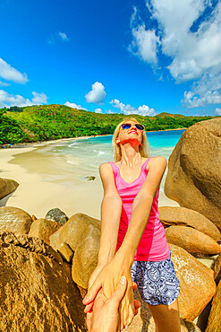 Tropical summer holidays. Follow me POV. Tourist woman holding hand of her friend at Praslin, Seychelles, Indian Ocean. Popular destination of pristine Anse Lazio Beach and turquoise sea on background