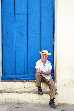 Local man relaxing on the street in Trinidad, Cuba, West Indies, Caribbean, Central America