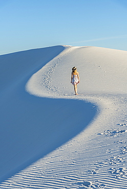 A woman walking along the S curve of a dune's ridge in White Sands National Park, New Mexico, United States of America, North America