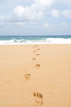 Footsteps on the beach leading into the ocean in the Hawaiian island of Kauai, Hawaii, United States of America, North America