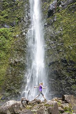 Hiker leaping in front of a waterfall along the famous Kalalau Trail, along Kauai's Na Pali Coast, Kauai, Hawaii, United States of America, North America