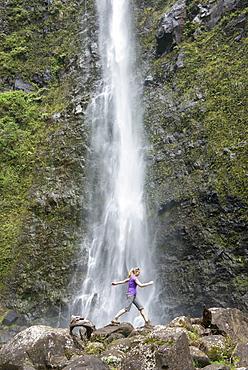 Hiker leaping in front of a waterfall along the famous Kalalau Trail, along Kauai's Na Pali Coast, Kauai, Hawaii, United States of America, North America