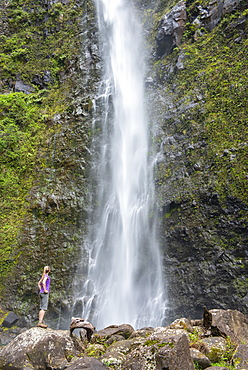 Hiker admiring a waterfall along the famous Kalalau Trail, along Kauai's Na Pali Coast, Kauai, Hawaii, United States of America, North America