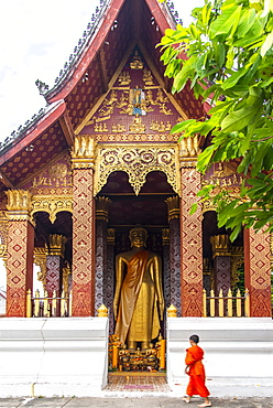 A young Buddhist monk stands before a large statue of Golden Buddha in Luang Prabang, Laos, Indochina, Southeast Asia, Asia