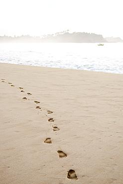 Footprints in the sand at sunrise on Talalla Beach, Sri Lanka, Asia