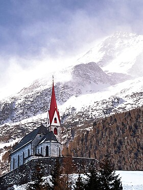 Church with a snowy mountains in the background with wind gusting on slopes and top, Trentino-Alto Adige, Italy, Europe