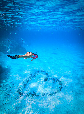 An athletic woman free-dives to inspect a heart arranged with rocks on the bottom of the ocean, French Polynesia, South Pacific islands, Pacific