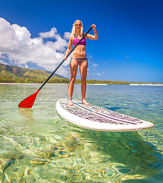 A young athletic woman using a stand-up paddle-board in a calm bay of Hawaii.