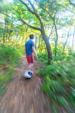 Christopher Brown rides his One-Wheel through a maritime forest near Nags Head, North Carolina USA