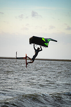 Pro surfer James Jenkins jumps his wing surfer over the Pamlico Sound at Nags Head, North Carolina, United States of America, North America