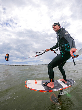 Photographer Skip Brown on his foiling kiteboard on the Pamlico Sound, Nags Head NC USA. MR