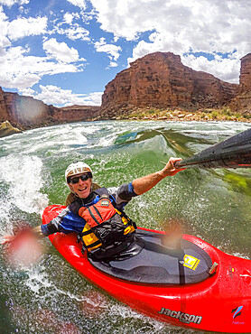Skip Brown surfs his whitewater kayak on a glassy standing wave on the Colorado River through the Grand Canyon. Arizona, USA MR