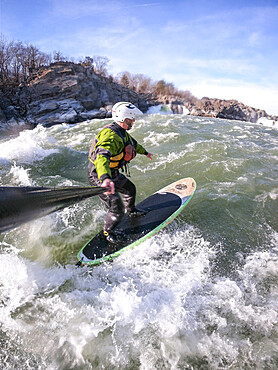 Photographer Skip Brown stand up paddle surfs in winter challenging whitewater below Great Falls of the Potomac River, USA. MR