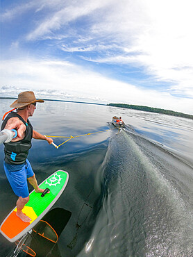 Photographer Skip Brown rides his hyrofoil behind a small boat on Sebago Lake, Maine USA. MR