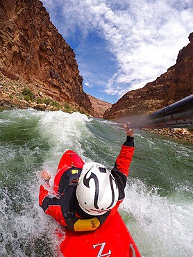 Skip Brown surfs his whitewater kayak on a glassy standing wave on the Colorado River through the Grand Canyon, USA MR Skip Br