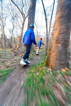Brothers ride their One-Wheels on a single track mountain biking trail next to the Potomac River. Bethesda, Maryland USA