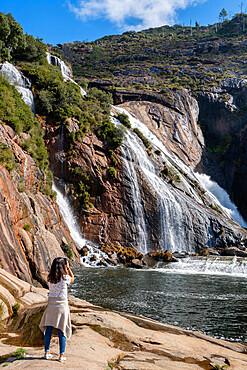 Caucasian woman photographing Ezaro waterfall with water crashing on lake between rocks in Galicia, Spain